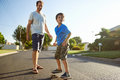 Father son skateboard young boy learning to ride as teaches him in the suburb street having fun Royalty Free Stock Images