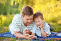 Father and son with a smartphone outdoors together Royalty Free Stock Image