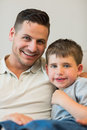 Father and son smiling together at home portrait of Stock Photo