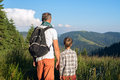 Father with son are standing on a alpine meadow among a lush gra Royalty Free Stock Photo