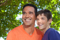 Father and son standing together in yard hispanic teenaged happily outside looking off into distance Stock Photos