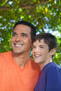 Father and son standing together in yard hispanic teenaged happily outside looking off into distance Stock Images
