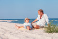 Father with son take a sun bath on the sea beach Royalty Free Stock Photo