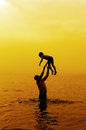 Father and son to the sea at sunset swimming in Stock Images