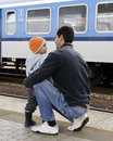 Father and son at train station waiting for a Royalty Free Stock Images