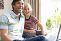 Father and son (6-8) using laptop computer, smiling, portrait Royalty Free Stock Photo