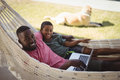 Father and son using laptop while relaxing on hammock Royalty Free Stock Photo