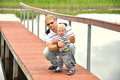 Father and son  on  a wooden pier near a river Royalty Free Stock Photos