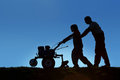 Father and son working the land with a tiller silhouettes of small scale organic farming concept Royalty Free Stock Image