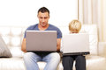 Father and son working on their computers on the sofa Royalty Free Stock Photo