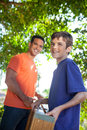 Father and son working together hispanic teenaged happily carry ladder outside in yard Royalty Free Stock Photography