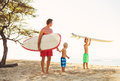 Father and sons going surfing two young at the beach Royalty Free Stock Photography