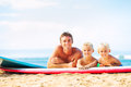 Father and sons going surfing two young at the beach Royalty Free Stock Images