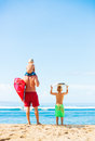 Father and sons going surfing young at the beach looking out at the ocean checking the waves Royalty Free Stock Photography