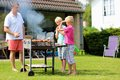 Father with sons grilling meat in the garden a two twin teenage boys cooking on barbecue for summer family dinner at backyard of Royalty Free Stock Photo