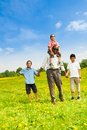Father with sons happy standing him and one on his shoulders Royalty Free Stock Photo