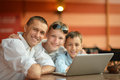 Father and sons with laptop at the table Stock Image