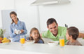 Father speaking to his children who are having breakfast with mother looking at them on the background Stock Image