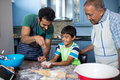 Father sprinkling flour on son hand while preparing food with grandfather