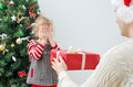 Father surprising little girl with christmas gift Stock Photos