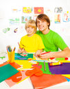 Father teach son to craft with little years old cut and glue with paper teaching boy Royalty Free Stock Photo