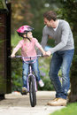 Father teaching daughter to ride bike in garden smiling Stock Image
