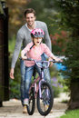 Father teaching daughter to ride bike in garden smiling Royalty Free Stock Images