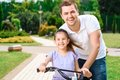 Father teaching daughter to ride a bike Royalty Free Stock Photo