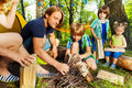 Father teaching his kids to make a camp fire Royalty Free Stock Photo