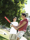 Father teaching son how to hold baseball bat standing on grass in park smiling tilt Royalty Free Stock Photo