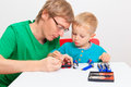 Father teaching son how to repair toy train learning and early education concept Stock Photo