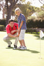 Father Teaching Son To Play Golf Stock Photo