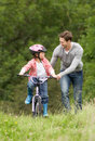 Father teaching son to ride bike in countryside smiling Stock Photos