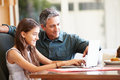 Father and teenage daughter looking at laptop together browsing the net smiling Royalty Free Stock Images