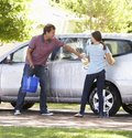 Father and teenage daughter washing car together Royalty Free Stock Images