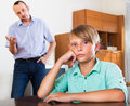 Father and teenage son argue ordinary his in the middle of at the room Royalty Free Stock Photo