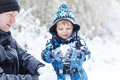 Father and toddler boy having fun with snow on winter day Stock Photos