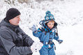 Father and toddler boy having fun with snow on winter day little preschool his playing first in forest Stock Images