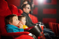 Father and two children, boys, watching cartoon movie in the cinema