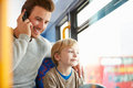 Father using mobile phone on bus journey with son sitting down smiling Stock Photos