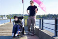 Father walking with disabled son out on lake pier six year old in wheelchair sunny day Stock Photo