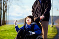 Father walking with disabled son in wheelchair at park Stock Images