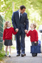 Father walking to school with children on way to work holding hands looking at son smiling Royalty Free Stock Image