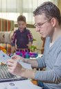 Father working in home office and son playing hard with notebook his boring on the background Royalty Free Stock Images