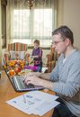 Father working in home office and son playing hard with notebook his boring on the background Royalty Free Stock Photos