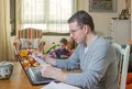 Father working in home office and son playing reading business documents his boring on the background Stock Photos