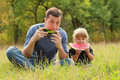 Father and young daughter eat watermelon in nature Royalty Free Stock Images