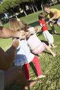 Fathers and children playing tug of war Stock Photo