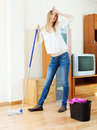 Fatigue long haired girl washing parquet floor with mop at home Stock Image