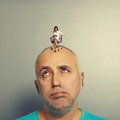 Fatigued man and small angry woman men women on his head over grey background Stock Images